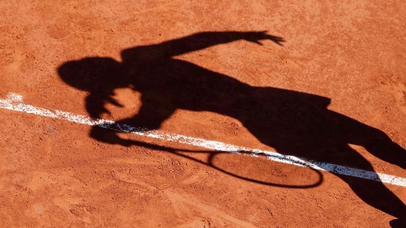 Latvia's Anastasija Sevastova cast her shadow on the clay court as she serves against Marketa Vondrousova of the Czech Republic during their fourth round match of the French Open tennis tournament at the Roland Garros stadium in Paris, Sunday, June 2, 2019. (AP Photo/Christophe Ena )