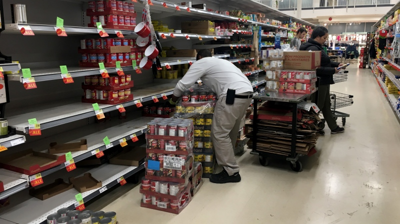 Workers restock grocery store shelves with canned goods early in the morning in Toronto on Friday March 13, 2020. THE CANADIAN PRESS/Frank Gunn