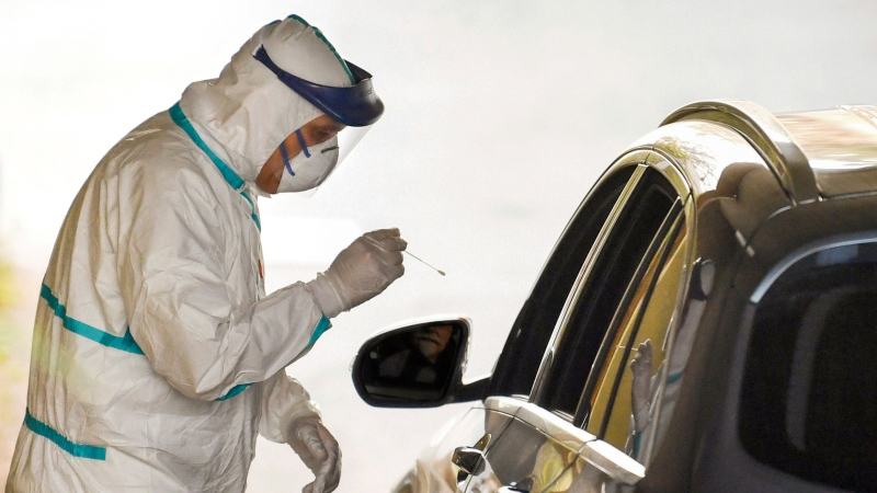 Drive-thru swabs for coronavirus are performed directly in cars, with minimum contact, in Bologna, Italy, Wednesday, March 18, 2020. For most people, the new coronavirus causes only mild or moderate symptoms. For some it can cause more severe illness, especially in older adults and people with existing health problems. (Massimo Paolone/LaPresse via AP)