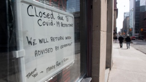 A sign in a barbershop window indicates the establishment is closed because of the COVID-19 virus in Ottawa, Wednesday, March 18, 2020. (THE CANADIAN PRESS / Adrian Wyld)