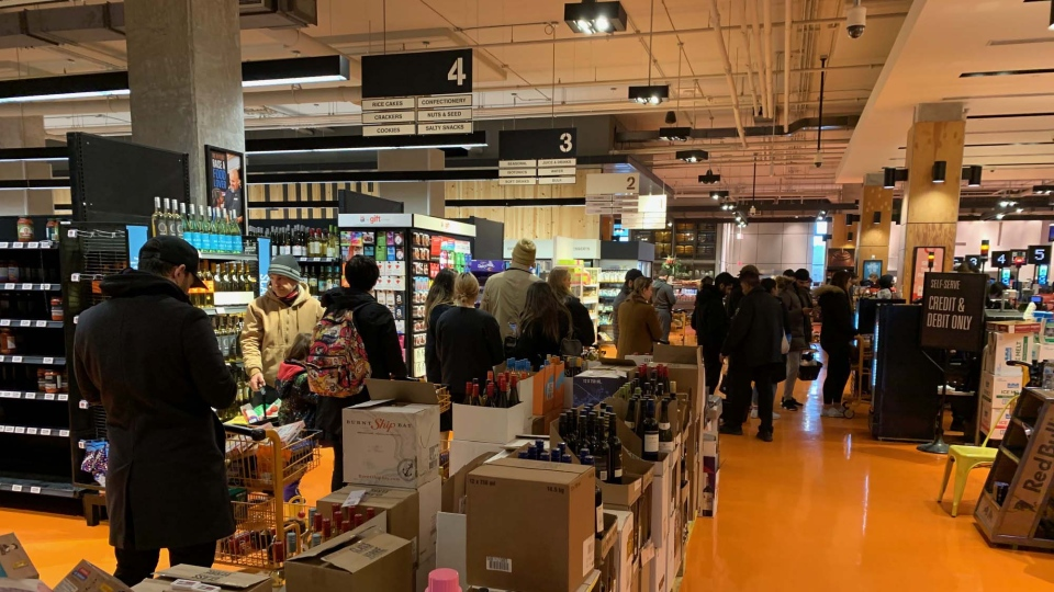Shoppers at a Toronto grocery store stand in long lines to buy groceries amid a stockpiling frenzy Tuesday March 17, 2020. (Joshua Freeman /CP24)