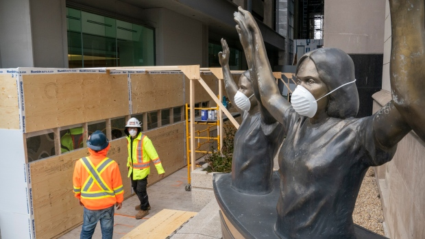 Masked statures stand guard as workmen build a temporary hallway to the Covid-19 testing centre at Mt. Sinai Hospital in Toronto on Thursday March 19, 2020. THE CANADIAN PRESS/Frank Gunn