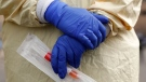 A nurse holds a swabs and test tube kit to test people for COVID-19, the disease that is caused by the new coronavirus, at a drive through station. (Paul Sancya/AP)