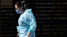 A hospital worker wearing a face shield and mask is seen at a COVID-19 assessment centre for staff at Lions Gate Hospital, in North Vancouver, on Thursday, March 19, 2020. THE CANADIAN PRESS/Darryl Dyck