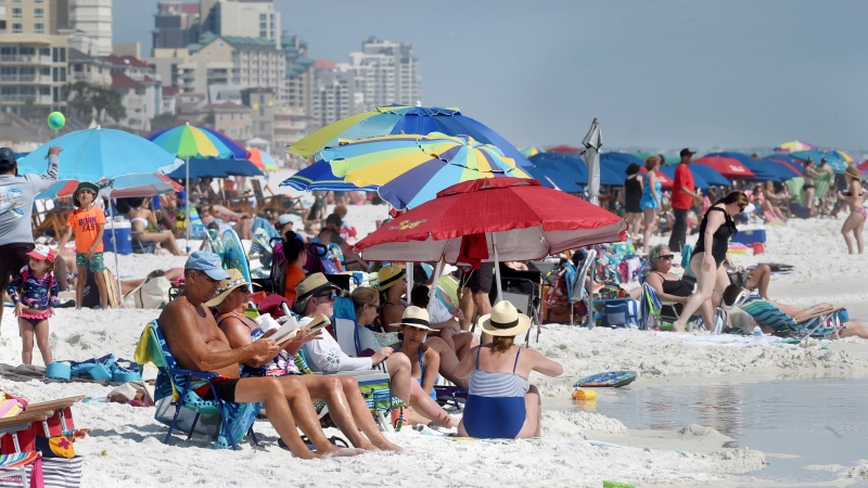 People gather on the shoreline in Destin, Fla., Wednesday, March 18, 2020. The Walton County Sheriff's Office announced deputies will be enforcing the executive order issued by Gov. Ron DeSantis to limit gatherings to no more than 10 people on public beaches, but will be looking for voluntary compliance rather than harder-edged enforcement. (Devon Ravine/Northwest Florida Daily News via AP)