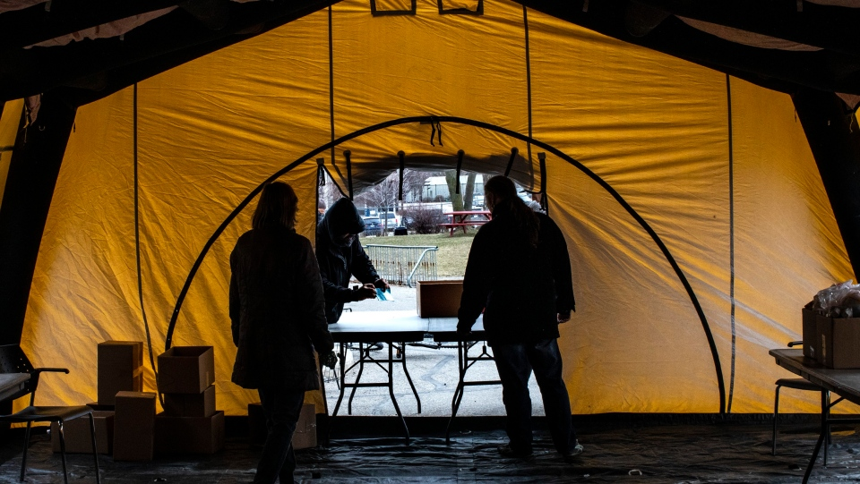 Staff members hand out provisions at the Daily Bread Food Bank in Toronto on Wednesday March 18, 2020. A tent has been temporarily erected outside the warehouse due to health concerns caused by the spead of the Corona Virus. THE CANADIAN PRESS/Chris Young