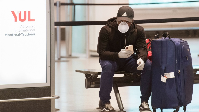 An airline passenger checks his smart phone at Montreal–Trudeau International Airport, Friday, March 20, 2020, as COVID-19 cases rise in Canada and around the world.THE CANADIAN PRESS/Graham Hughes