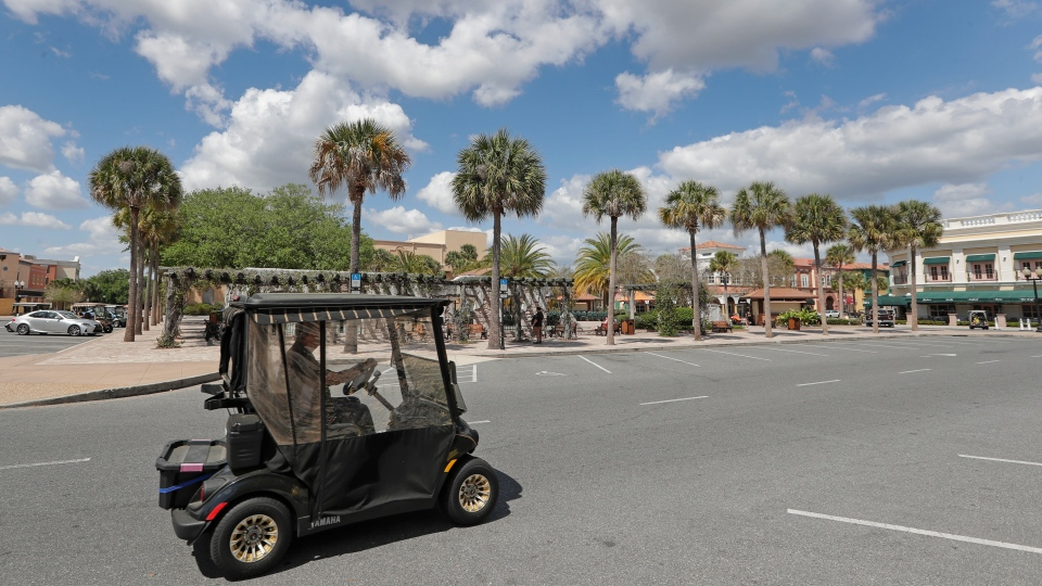 In this Thursday, March 19, 2020 photo, a resident drives his golf cart down what usually is a busy street by the Spanish Springs town square in The Villages, Fla. (AP Photo/John Raoux)