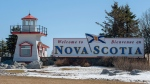 FILE- Travellers are greeted as they arrive in Nova Scotia near Amherst, N.S. on Sunday, March 22, 2020. Premier Stephen McNeil announced anyone entering Nova Scotia, apart from those deemed essential workers, must now self-isolate for 14 days. THE CANADIAN PRESS/Andrew Vaughan