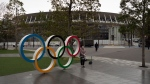 A woman pauses for photos next to the Olympic rings near the New National Stadium in Tokyo, Monday, March 23, 2020. (AP Photo/Jae C. Hong)