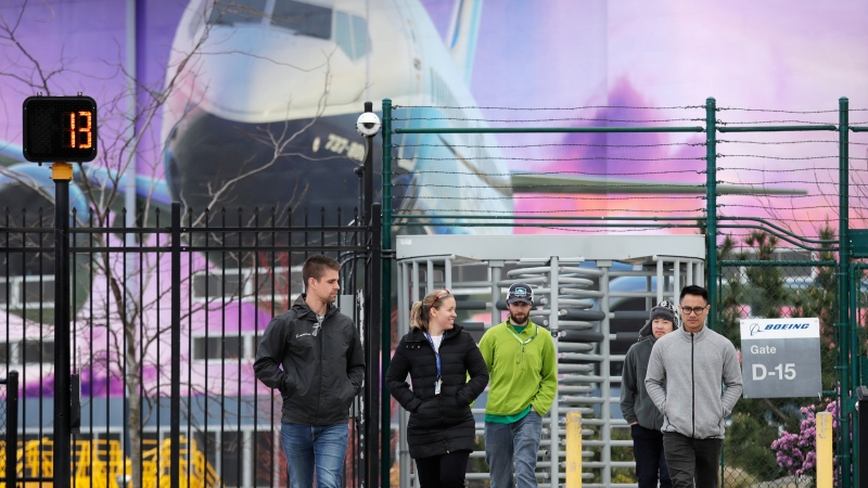 Workers head out a gate at a Boeing airplane manufacturing plant, where a mural of a jet covers a massive door behind, Monday, March 23, 2020, outside Seattle, in Renton, Wash. Boeing is suspending operations at its Seattle area facilities due to the spread of coronavirus in the area, where dozens of people have died. Operations would be reduced beginning Wednesday, the company said in a statement, and production would be suspended for a two weeks. (AP Photo/Elaine Thompson)