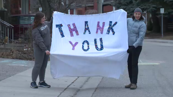 Residents of Shanley Street in Kitchener hold up a sign that reads,