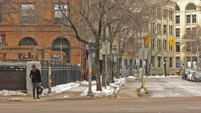 A lone pedestrian stands along Main street on Sunday, March 22, 2020. (Source: Dan Timmerman/ CTV News Winnipeg)