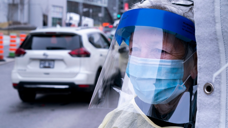 A health care worker waits for the next car at a walk-in COVID-19 test clinic in Montreal on Monday, March 23, 2020. THE CANADIAN PRESS/Paul Chiasson