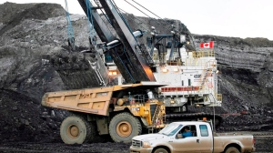 A pickup truck passes a mining shovel filling a haul truck at an oilsands mine near Fort McMurray, Alta., in this July 9, 2008 file photo. THE CANADIAN PRESS/Jeff McIntosh