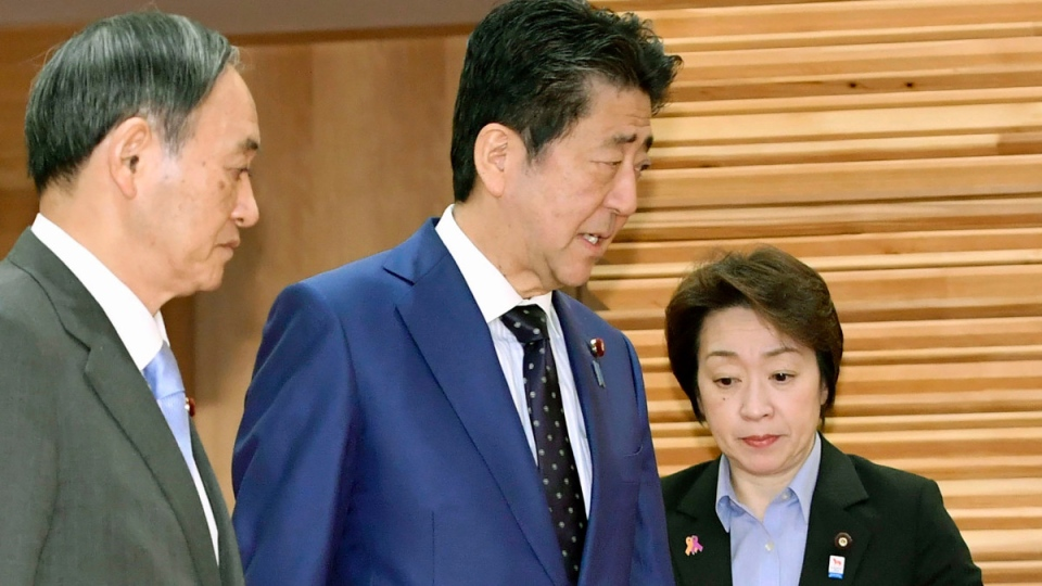 Japanese Prime Minister Shinzo Abe, centre, walks past Olympic Minister Seiko Hashimoto, right, to attend a cabinet meeting at his official residence in Tokyo, on March 24, 2020. (Yoshitaka Sugawara / Kyodo News via AP)