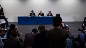 Tokyo 2020 Organizing Committee president Yoshiro Mori, center, and CEO Toshiro Muto, right, attend a news conference in Tokyo, Tuesday, March 24, 2020. (AP Photo/Jae C. Hong)