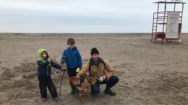 Fraser Teeple, right, along with his children, Sawyer and Wes, and dog Timber enjoy the early morning quiet on Port Stanley Beach, Tuesday, March 24, 2020. (Sean Irvine / CTV London)