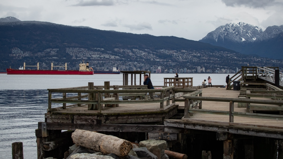 People stand on the Jericho Pier, in Vancouver, on Monday, March 23, 2020. (Darryl Dyck / THE CANADIAN PRESS)