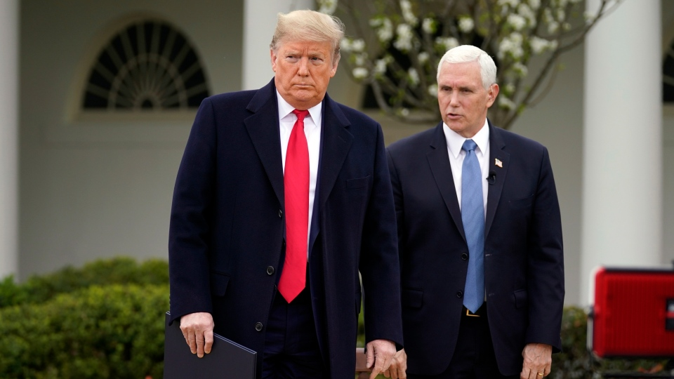 U.S. President Donald Trump speaks with Vice President Mike Pence as they arrive for a Fox News Channel virtual town hall, at the White House, Tuesday, March 24, 2020, in Washington. (AP Photo/Evan Vucci)