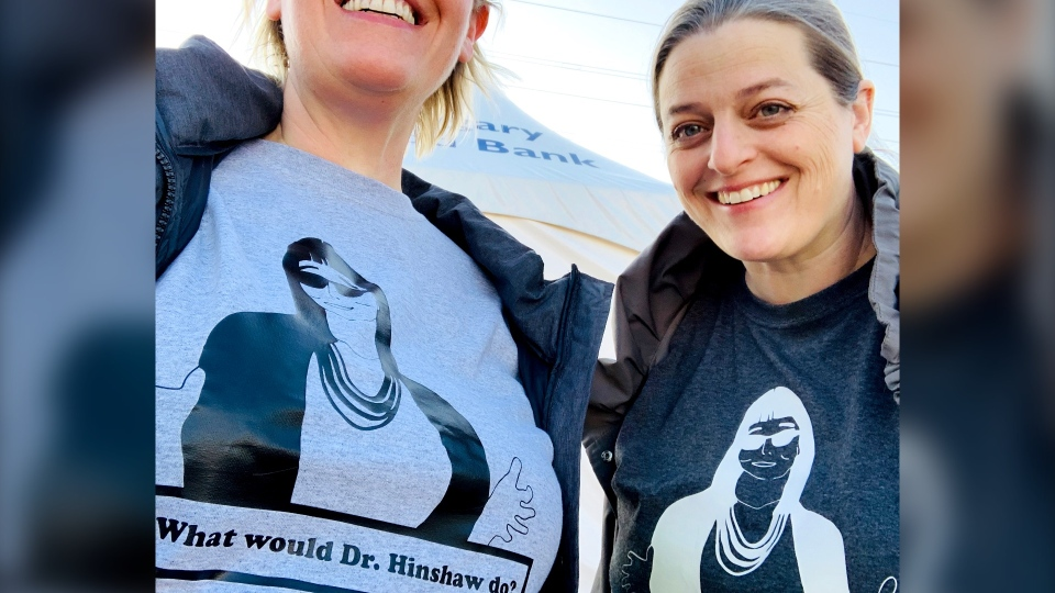 Alison Van Rosendaal, right, and sister Julie Van Rosendaal model shirts with a drawing of Dr. Deena Hinshaw that were sold with funds going to Alberta food banks, (Courtesy Julie Van Rosendaal)