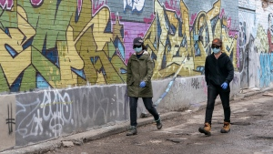 Two women wear masks as they walk down a graffiti covered alley in Toronto on Tuesday March 24, 2020. THE CANADIAN PRESS/Frank Gunn