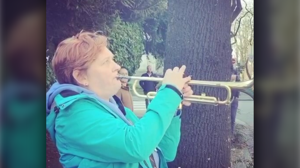 Samantha Monckton plays the trumpet on the street for her father, who is stuck inside a Vancouver care home after being diagnosed with COVID-19. (Facebook)