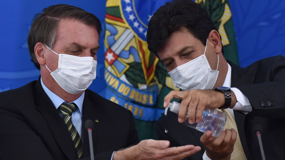 Wearing masks, Brazil's Health Minister Luiz Henrique Mandetta, right, applies alcohol gel on hands of President Jair Bolsonaro's hands during a press conference on the new coronavirus, at the Planalto Presidential Palace in Brasilia, Brazil, Wednesday, March 18, 2020. (AP Photo/Andre Borges)