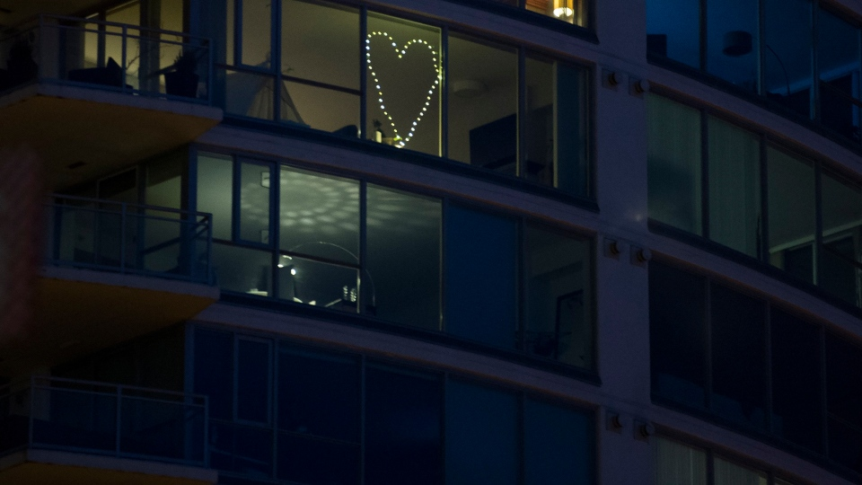 A condo is seen with a string of lights in the shape of a heart in Vancouver, B.C. Tuesday, March 24, 2020. THE CANADIAN PRESS/Jonathan Hayward