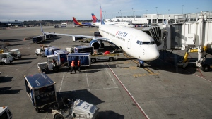 A ground crew prepares to unload luggage from an arriving Delta Airlines flight at the Seattle-Tacoma International Airport on March 15, 2020 in Seattle, Washington. (John Moore / Getty Images / CNN)