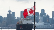 Downtown Vancouver is pictured in the background as a Canadian flag blows in the wind at the Lonsdale Quay in North Vancouver, B.C., on March 24, 2020. (Jonathan Hayward / THE CANADIAN PRESS)