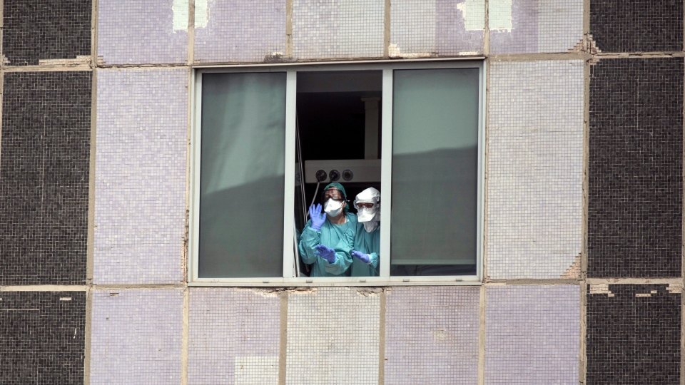 In this Wednesday, March 18, 2020 file photo, medical workers wearing face masks gesture from hospital La Paz in Madrid, Spain. (AP Photo/Manu Fernandez)