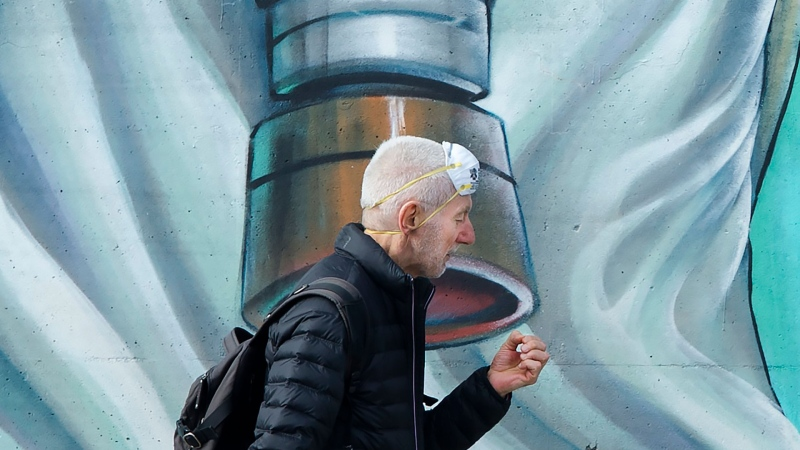 A man wearing a mask on his head walks past a graffiti mural in Toronto on Wednesday, March 25, 2020. THE CANADIAN PRESS/Nathan Denette