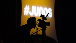 """A videographer looks through his camera during the 2020 Juno Award nominee press conference in Toronto on January 28, 2020. Organizers behind the annual celebration of Canadian music say they've decided to """"hold off indefinitely"""" on revealing who picked up this year's Junos trophies, as the country deals with the COVID-19 pandemic. THE CANADIAN PRESS/Nathan Denette"""