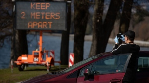 A sign warns people to social distance and keep at least two metres apart from one another due to concerns about the spread of the coronavirus, as a motorist wearing a protective face mask and gloves stops to take a photograph, in Vancouver, on Wednesday, March 25, 2020. THE CANADIAN PRESS/Darryl Dyck