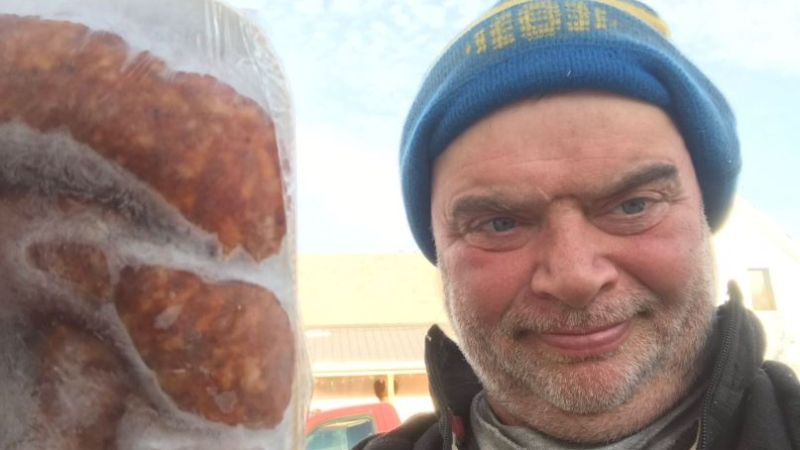 Prince Edward Island pork farmer Ranald MacFarlane with one of his frozen hams for sale at his physically-distanced backyard drive-thru. (Ranald MacFarlane)