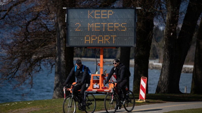 A sign warns people to social distance and keep at least 2 metres apart from one another due to concerns about the spread of the coronavirus, as two men ride bicycles on the seawall, in Vancouver, on Wednesday, March 25, 2020. (Darryl Dyck / THE CANADIAN PRESS)