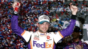 In this Monday, Feb. 17, 2020 file photo,Denny Hamlin celebrates in Victory Lane after winning the NASCAR Daytona 500 auto race at Daytona International Speedway in Daytona Beach, Fla. NASCAR eased off the brake in the real sports world brought to a sudden halt by the coronavirus and introduced the country to iRacing with some of the sports biggest stars. Hamlin, the three-time Daytona 500 winner, beat Dale Earnhardt Jr. off the final corner Sunday, March 22, 2020 at virtual Homestead-Miami Speedway to win the bizarre spectacle. (AP Photo/John Raoux, File)