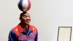 "In this Dec. 10, 2010, file photo, Harlem Globetrotters Fred ""Curly"" Neal spins a ball on his head prior to the bidding for the Naismith Rules, the original rules for basketball, framed at right, at Sotheby's in New York. Neal, the dribbling wizard who entertained millions with the Harlem Globetrotters for parts of three decades, has died the Globetrotters announced Thursday, March 26, 2020. He was 77. Neal played for the Globetrotters from 1963-85, appearing in more than 6,000 games in 97 countries for the exhibition team known for its combination of comedy and athleticism. (AP Photo/Richard Drew, File)"
