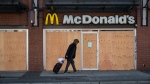 A man walks past a McDonald's restaurant with boarded up windows in the Downtown Eastside of Vancouver, B.C. on Wednesday, March 25, 2020. (THE CANADIAN PRESS/Darryl Dyck)