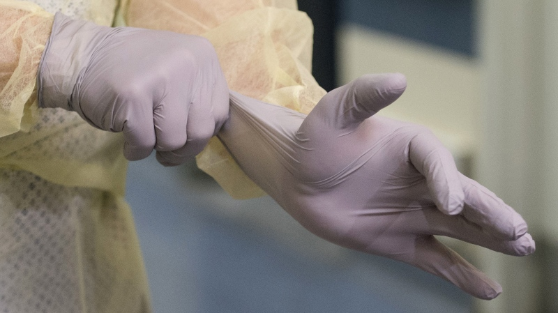 A man demonstrates how to put on a surgical gloves and other protective clothing during a tour of a COVID-19 evaluation clinic in Montreal, Tuesday, March 10, 2020. Dirty money has taken on a new meaning as the war on the novel coronavirus ramps up. THE CANADIAN PRESS/Graham Hughes