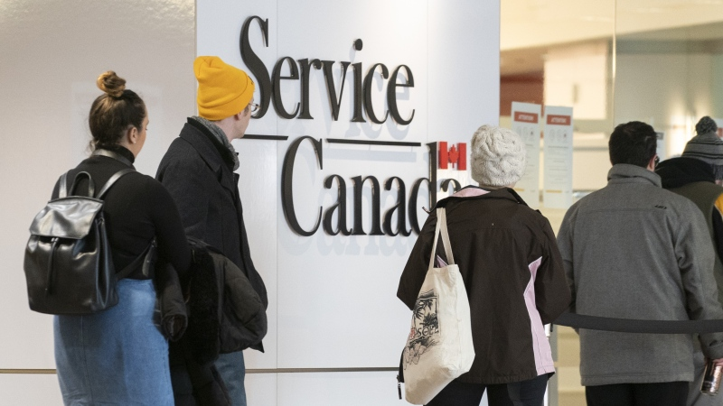 People line up at a Service Canada office in Montreal on Thursday, March 19, 2020. THE CANADIAN PRESS/Paul Chiasson