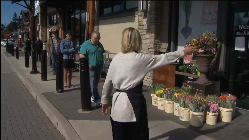A florist does crowd control at Stong's Market in North Vancouver during the coronavirus pandemic. (CTV)