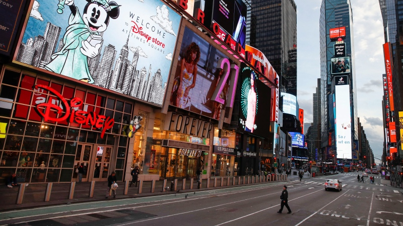 FILE - In this March 20, 2020, file photo, a police officer walks across an empty Seventh Avenue in a sparsely populated Times Square due to COVID-19 concerns in New York. (AP Photo/John Minchillo, File)