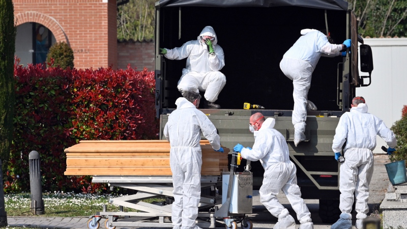 FILE - In this March 21, 2020 file photo, coffins are downloaded at the Ferrara cemetery, northern Italy, from a military convoy coming from Bergamo, a city at the epicenter of the coronavirus outbreak in northern Italy. (Massimo Paolone/LaPresse via AP, file)