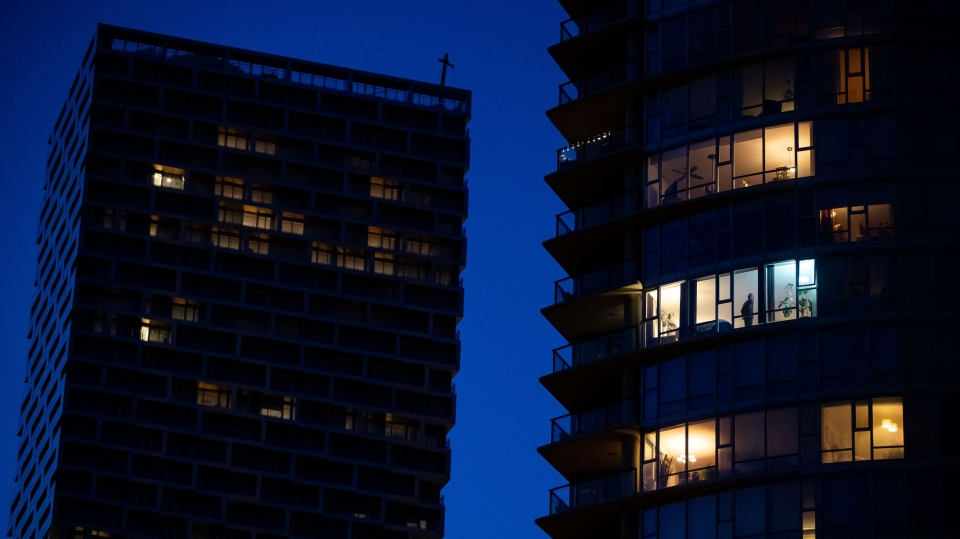 A man stands in the window of an upper floor condo as people have been urged to stay home to help prevent the spread of the coronavirus, in Vancouver, on Tuesday, March 24, 2020. THE CANADIAN PRESS/Darryl Dyck