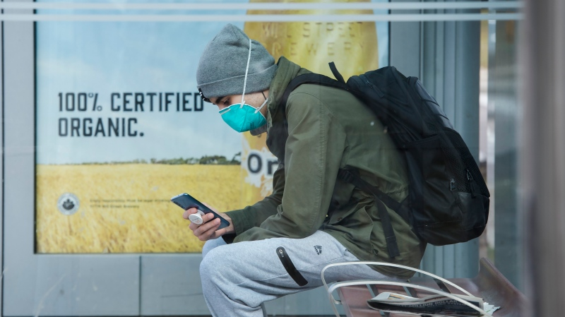A man wears a mask while sitting in a bus shelter in Toronto on Friday, March 27, 2020. People are taking extra measures against the spread of the coronavirus also known as COVID-19. THE CANADIAN PRESS/Nathan Denette