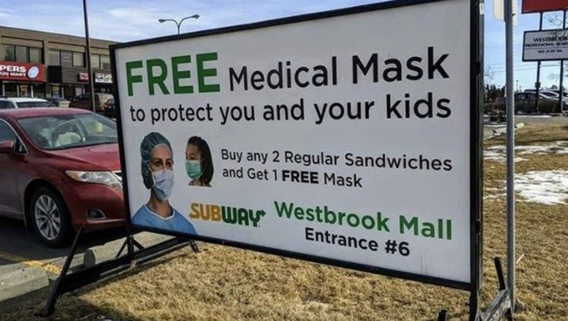 The advertisement, posted outside Westbrook Mall in Calgary, offered customers a free medical mask with a sandwich purchase. (Twitter/@Erin_Crook)