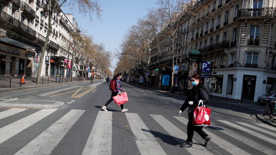 People wearing protective masks cross the deserted Boulevard Sebastopol during the lockdown of coronavirus, in Paris, Friday, March 27, 2020.  (AP Photo/Francois Mori)