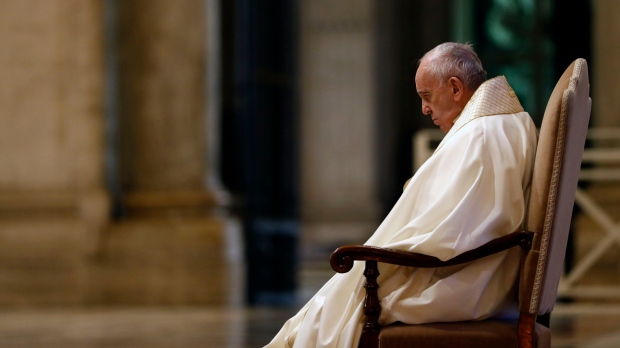 """Pope Francis sits in at the entrance of St. Peter's Basilica, at the Vatican, Friday, March 27, 2020. Praying in a desolately empty St. Peter's Square, Pope Francis on Friday likened the coronavirus pandemic to a storm laying bare illusions that people can be self-sufficient and instead finds """"all of us fragile and disoriented"""" and needing each other's help and comfort. (Yara Nardi/Pool Photo via AP)"""